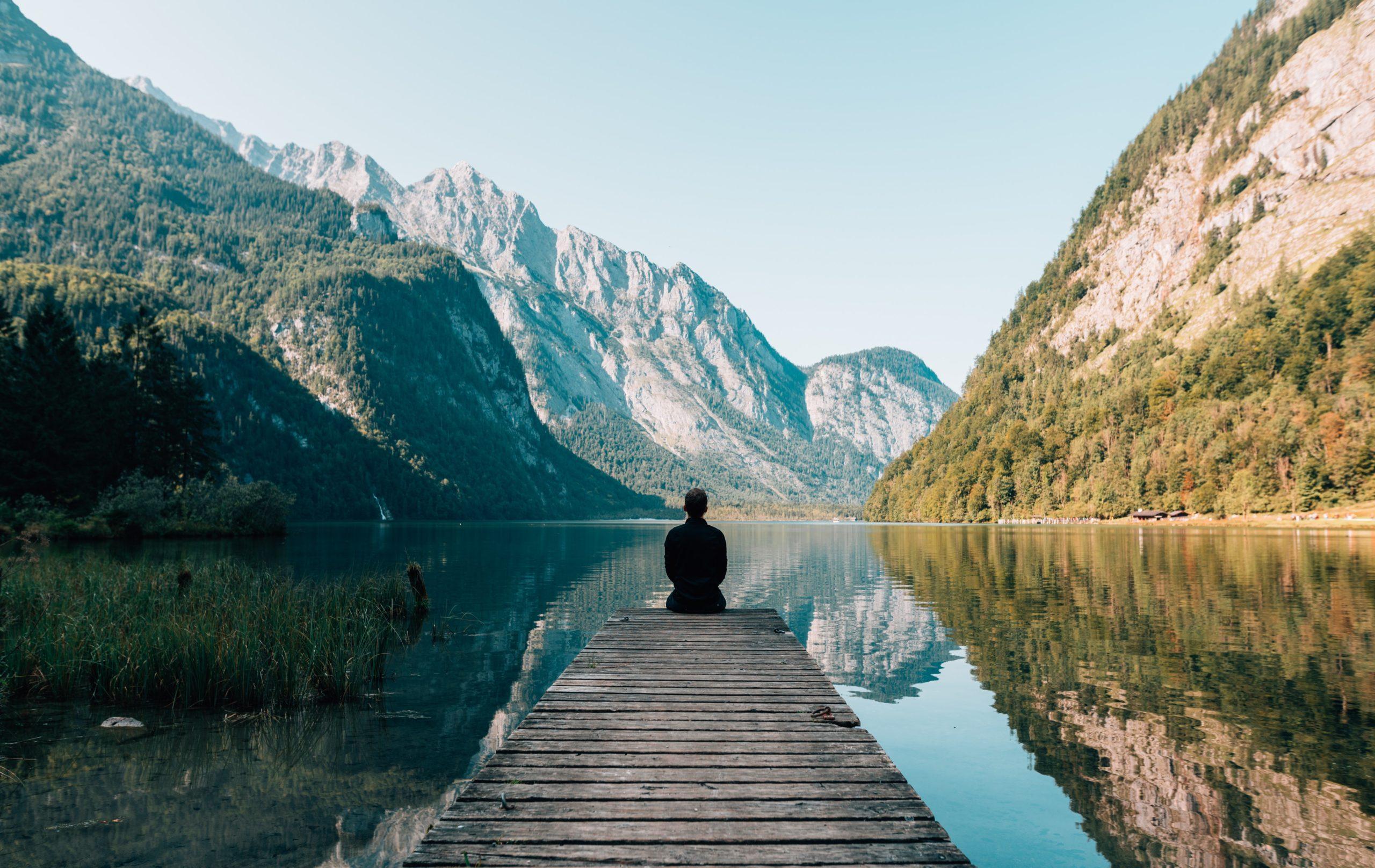 homme médite au bord d'un lac